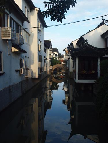 裏通りの運河に架かる丸い橋と白壁が印象的